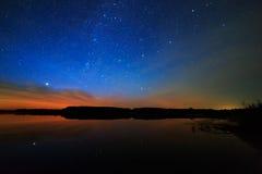 Ochtenddageraad op sterrige hemel als achtergrond die in het water wordt weerspiegeld Stock Foto