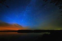 Ochtenddageraad op sterrige hemel als achtergrond die in het water wordt weerspiegeld Stock Foto's
