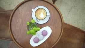 Ochtendespresso met Frans macaronsdessert op de houten lijstachtergrond in koffie, top down mening stock video