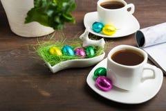 Ochtendkoffie in Pasen met paar van koffie en chocoladeeieren stock foto's