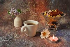 Ochtendkoffie in zeven haasten: een kop koffie, bloemen in een vaas, droge vruchten en snoepjes in een vaas, een brandende kaars royalty-vrije stock afbeelding