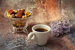 Ochtendkoffie in zeven haasten: een kop koffie, bloemen in een vaas, droge vruchten en snoepjes in een vaas, een brandende kaars stock foto's