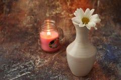 Ochtendkoffie in zeven haasten: een kop koffie, bloemen in een vaas, droge vruchten en snoepjes in een vaas, een brandende kaars stock afbeelding
