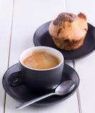 Ochtendkoffie in zwarte kop met erachter muffin royalty-vrije stock fotografie