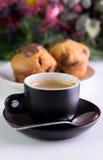 Ochtendkoffie in zwarte kop met erachter muffins royalty-vrije stock afbeelding