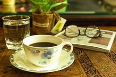 Ochtendlicht met koffiekop en glas water bij het snijden van hout stock afbeelding