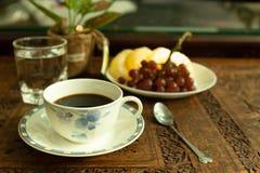 Ochtendlicht met koffiekop en glas water en vers fruit royalty-vrije stock foto