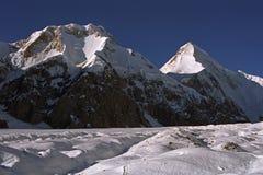 Ochtendmening aan Chapaev-piek 6371m op linkerzijde en Khan Tengri-piek 6995m stock afbeeldingen