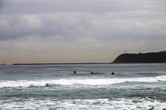 Ochtendmening van Surfers en Strand tegen Bluff royalty-vrije stock afbeelding