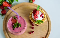 Ochtendontbijt met aardbei smothie en wafels met slagroom en bessen royalty-vrije stock fotografie