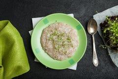 Ochtendontbijt, organisch havermeel met micro- greens op een zwarte achtergrond Een handdoek, een uitstekende lepel en jonge sala stock afbeeldingen