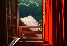 Ochtendzon die door het venster met een kop van koffie op het venster nog gluurt royalty-vrije stock fotografie
