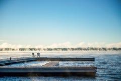 Ochtendzonsopgang op een dok met de Stoelen en de mist van Muskoka Royalty-vrije Stock Foto