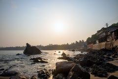 ochtendzonsopgang op het rotsachtige overzeese strand royalty-vrije stock afbeelding