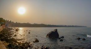 ochtendzonsopgang op het rotsachtige overzeese strand stock afbeeldingen