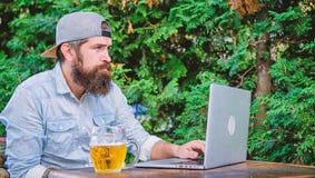 Ocio brutal del hombre con la cerveza y el ordenador port?til Finalmente viernes El inconformista se relaja para sentar la terraz imagen de archivo