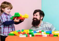 Ocio de la familia Juego del hijo del padre El padre y el hijo crean construcciones Juego barbudo del hombre y del hijo junto Cad fotografía de archivo