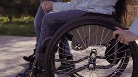 Ocio de la familia Mujer discapacitada joven en silla de ruedas con su madre que camina cerca del mar, hablando y divirtiéndose almacen de metraje de vídeo