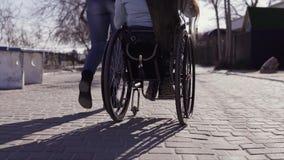 Ocio de la familia Mujer discapacitada joven en silla de ruedas con su madre que camina cerca del mar, hablando y divirtiéndose almacen de video