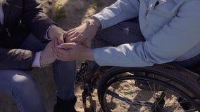 Ocio de la familia Mujer perjudicada discapacitada de los jóvenes en la silla de ruedas que habla con su madre que se sienta cerc almacen de video