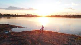 Ocio de la familia - padre y su hijo en ropa de los pares que caminan en la pesca de las manos que se sostienen - puesta del sol almacen de video
