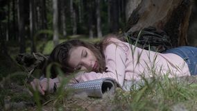 Ocio de la muchacha que acampa hermosa que se acuesta y que se enfría en la hierba profundamente en el bosque - metrajes