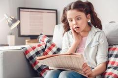 Ocio de la niña en casa que se sienta leyendo las noticias chocadas imagen de archivo