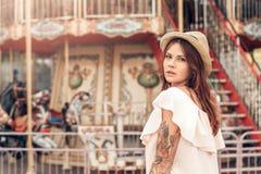 Ocio de Ourdoors Muchacha en la situación del sombrero en el parque de atracciones que mira detrás la cámara pensativa imagen de archivo libre de regalías