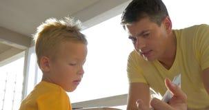 Ocio del gasto del padre y del niño con el libro almacen de metraje de vídeo