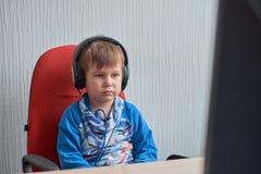 Ocio, educación, niños, tecnología y concepto de la gente - muchacho con el ordenador y los auriculares en la oficina Foto de archivo