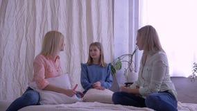 Ocio, madre e hijas de la familia charlando y divertirse junto en cama en casa metrajes