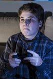Ocio. muchacho con la palanca de mando que juega al juego de ordenador en casa. Fotografía de archivo libre de regalías