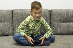 Ocio, niños, tecnología y concepto de la gente - muchacho sonriente con la palanca de mando que juega al videojuego en casa Fotos de archivo libres de regalías