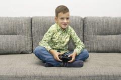 Ocio, niños, tecnología y concepto de la gente - muchacho sonriente con la palanca de mando que juega al videojuego en casa Fotografía de archivo libre de regalías