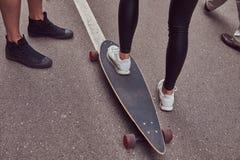 Ocio y concepto de los deportes - primer de los pies adolescentes de los pares con un longboard en una calle Imagen de archivo libre de regalías
