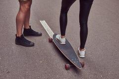 Ocio y concepto de los deportes - primer de los pies adolescentes de los pares con un longboard en una calle Fotos de archivo libres de regalías