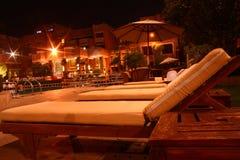 Ocioso al aire libre de madera para la piscina en la noche Imagenes de archivo