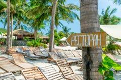 Ociosos de la abundancia en la playa arenosa con las palmas e indicador en el árbol fotos de archivo
