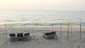 Ociosos de la playa debajo de los toldos en la arena contra el océano por la tarde almacen de video