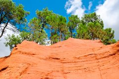 Ockerhaltige Ablagerung Roussillon: Blauer Himmel, schöne rote Hügel und grüne Kiefern lizenzfreie stockbilder