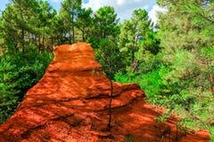 Ockerhaltige Ablagerung Roussillon: Schöne grüne Kiefern und große rote ockerhaltige Spitze stockbilder