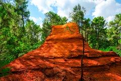 Ockerhaltige Ablagerung Roussillon: Schöne grüne Kiefern und großer roter Felsen stockfotografie