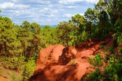 Ockerhaltige Ablagerung Roussillon: Schöne grüne Kiefern und orange Felsen stockfoto
