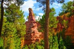 Ockerhaltige Ablagerung Roussillon: Schöne große rote ockerhaltige Spitze, blauer Himmel mit Wolken und grüne Kiefern lizenzfreies stockbild