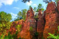 Ockerhaltige Ablagerung Roussillon: Schöne Kiefern in der orange Schlucht lizenzfreies stockbild