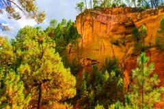 Ockerhaltige Ablagerung Roussillon: Schöne Kiefern und orange Felsen lizenzfreie stockbilder
