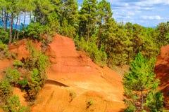 Ockerhaltige Ablagerung Roussillon: Schöne orange Hügel und üppige grüne Kiefern stockfotografie