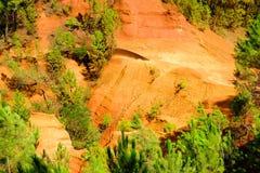 Ockerhaltige Ablagerung Roussillon: Schöne orange Hügel und grüne Kiefern lizenzfreies stockbild