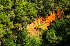Ockerhaltige Ablagerung Roussillon: Schöne orange Klippen und grüne Kiefern stockfotos