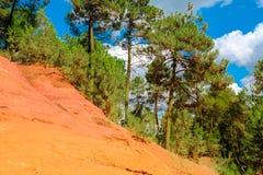 Ockerhaltige Ablagerung Roussillon: Schöne rote Hügel, blauer Himmel und grüne Kiefern lizenzfreie stockfotos